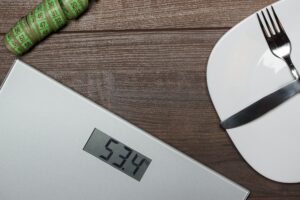 Dieting Concept With Scales On Wooden Floor